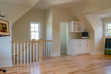 Tighter shot of the stairwell wall, cabinetry, and half bath
