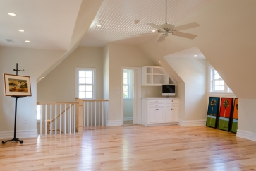 Stairwell wall, with cabinetry and half bath